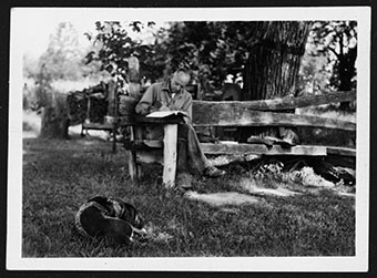 Aldo Leopold's essays on science, policy, and ethics remain highly influential. Here is he writing with his dog Flick by his side. Photo courtesy of the Aldo Leopold Foundation.
