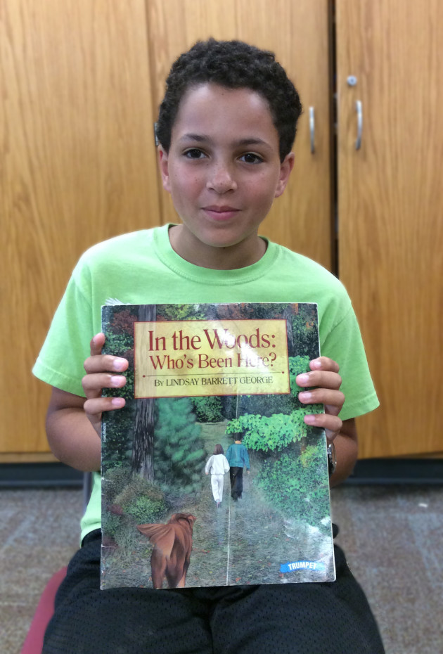 "Sawyer Gibson with his birthday book ""In the Woods: Who's Been Here?"" by Lindsay Barrett George. He and his brother Tanner received the book for their first and third birthdays and ask ""Who's been here?"" to explore nature to this day."