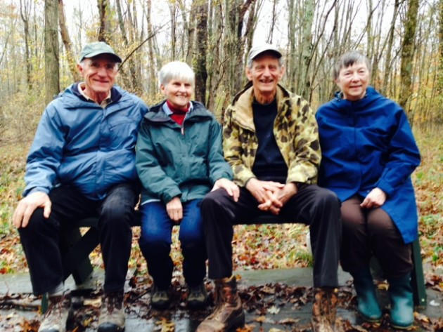 Scott and Ruth Sanders (left) with John and Beth Gallman take a seat in the woods on a new bench named in honor of John.