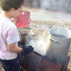 Sawyer scoops out impurities from the cooking sap. Warming pots sit atop the main cooking pan and a coffee can with a nail hole allows warmed sap to enter boiling sap without taking away the boil.