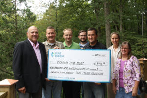 Duke Energy employees pose with Sycamore staff during a grant presentation at Cedar Crest